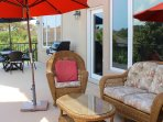 The back deck has wicker furnishings and dining table.