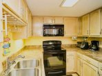 Well equipped kitchen has full size appliances, everything needed for meal preparation and serving.