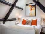 The master bedroom, with exposed oak beams and a king size bed