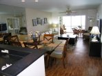 Open living space flows from kitchen to dining area to living room to lanai