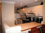 Fully equipped kitchen opens to living/dining area and window/door overlooking the bay and boat docks