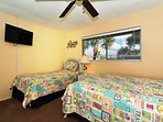 2nd Bedroom with queen plus twin-size beds, HDTV, large window overlooking bay and boat docks
