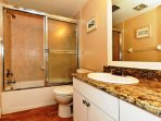 2nd bathroom with granite counters, tiled floors and shower surround