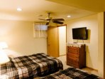 Third bedroom has dresser and flat screen TV.