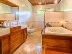 Shared bathroom with double sinks, stand alone shower, jetted tub and bidet.