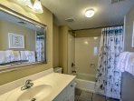 This en-suite bathroom features a shower/tub combo and single vanity.