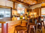 Breakfast bar with overhead wine glass rack. Fully equipped kitchen.