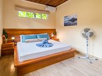 First bedroom with king bed, satellite tv and view of pool area.