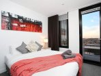 Second bedroom with queen bed, overlooking views to the city suburbs
