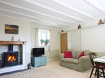 Cartwheel Cottage Lounge and diner with original floorboards and fireplace and cosy wood burner