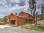 The beautiful log cabin is situated on 12.5 acres of mountainous land surrounded by towering trees.