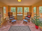 The sun room features comfortable chairs, a small library and splendid views of the surrounding greenery.