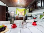 Fully equipped kitchen with microwave, stove, fridge, toaster, pots and pans.