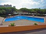 la piscina y piscina de niños con tumbonas, mesas, sillas  y sombrillas