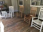 Front porch full of rocking chairs.