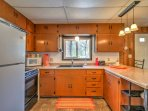 This well-equipped kitchen includes a stove top, oven, double sink, microwave and full size fridge.
