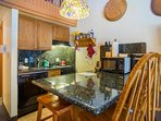The fully equipped kitchen with stove-top oven, dishwasher, microwave and coffee maker.
