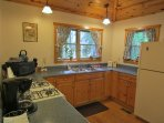 Kitchen has lots of cabinets & countertops; stocked with coffee, spices, lots of cookware & utensils