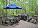 The large deck has a patio table, 6 chairs, bench, propane grill and soft outdoor lighting.
