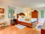 Spacious master bedroom with California king bed and direct access to tropical courtyard