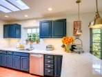 A bright and sunny kitchen with windows to the lush landscape, skylight and abundant counter space