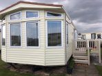 Outside caravan  lockable gated seating area with rattan sofa 2 chairs pub  Bench on grassed area