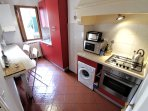 kitchen with washing machine, fridge, traditional oven, microwave and toaster