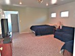 Bedroom above pool table room with queen, full, love seat couch and large flat screen tv