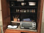Dry Kitchen set up to cook family meals. Oven, toaster, hot plate,spices, wraps, dishware and pots.