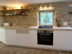 Fully equipped kitchen with natural stone working plate and dishwasher