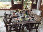 Veranda con tavolo da pranzo in legno e poltrone.