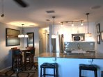 Well equipped kitchen with breakfast bar, refrigerator, microwave, & ice maker