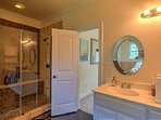 The master bedroom's his-and-hers bathroom features a pristine river stone shower.