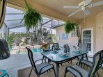 Comfortable outdoor dining in a covered Lanai with ceiling fan.