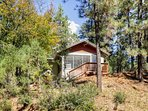 The cabin is nestled steps from the forest and the Ruidoso River.