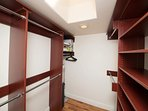 Walk in closet with plenty of space for folded clothes hangers and luggage/traveling bags