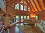 Cathedral ceilings, rustic wood beams, and floor-to-ceiling windows create the quintessential cabin feel.