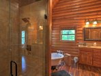 A large ensuite bathroom features a walk-in shower and a clawfoot tub.