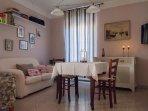 Caratteristico ed accogliete soggiorno, con TV a schermo piatto, poltroncina, divano e tavolo.