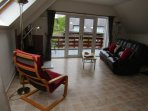 a large living room with a sofa, and leatherchair,  there is a log fire with a  basket of fire wood