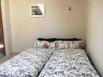 Zweites kleineres Schlafzimmer mit einem Doppelbett.