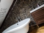 Attic bathroom with double vanity unit and roll top bath, exposing 1801 original stone walls