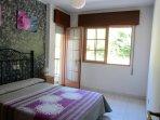 Dormitorio con cama de matrimonio y balcón.