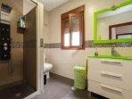 Amplio cuarto de baño con dos duchas y suelo de piedra pizarra.
