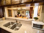 Kitchen with granite counteres, stainless appliances &dishwasher, dishes, utensils, pots &; pans.