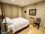 Master bedroom with queen bed, bamboo floors, and half bath.