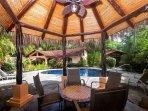 Palm thatched gazebo next to pool