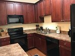 Kitchen has microwave, stove, dishwasher and full size refrigerator.