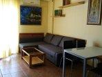 zona de salon comedor con sofa-cama nuevo y aire acondicionado