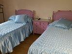 Habitación de 2 camas. Mesita, galán, armario y TV.